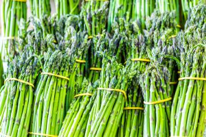 Closeup of many asparagus bunches on display at farmers market during summer
