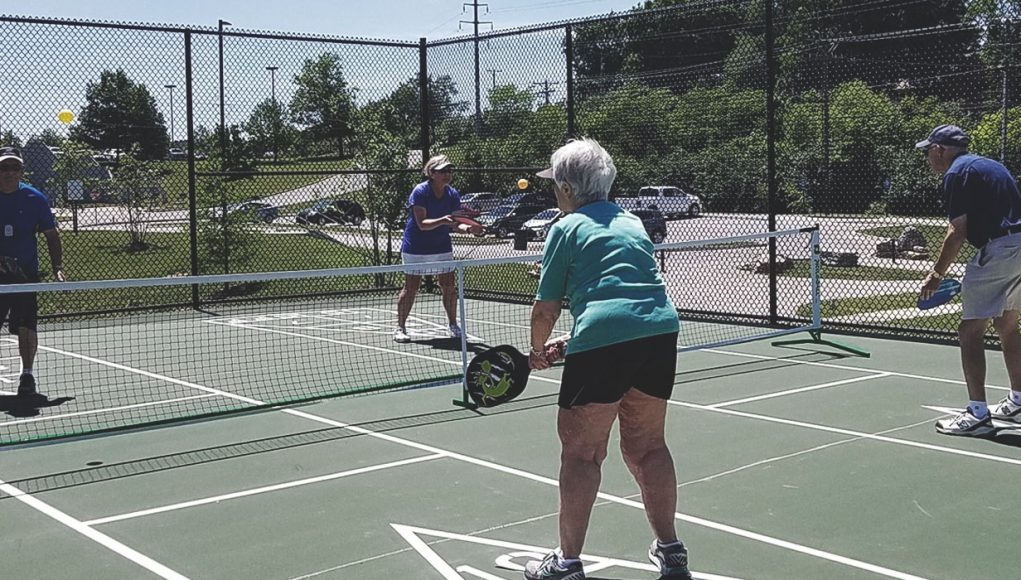 Senior adults outside playing pickle ball