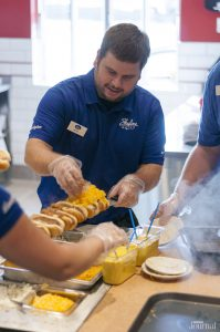 Skyline Chili worker putting cheese on coneys