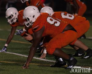 Fayette County: football players in orange uniforms on a field