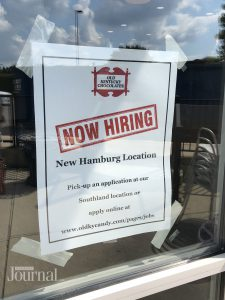 Now Hiring sign posted on door