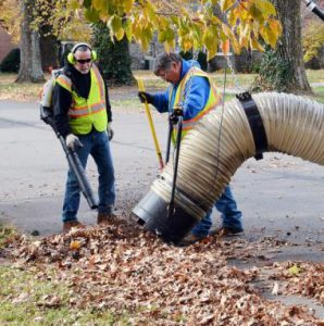 leaf collection: two men holding a large vacuum collection leaves