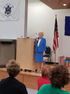 older woman in a blue suit talking on stage