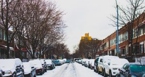 district 7: snow in the street with cars lining it and snow on top