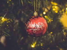 holiday: red ornament that says celebrate hanging on a tree