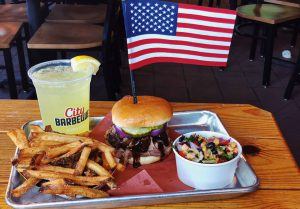 city barbeque meal with a drink and an american flag in the sandwich