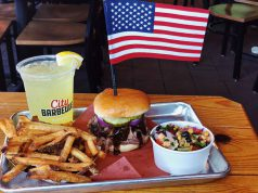 tray of fries, burger, southern mix, lemonade, and an american flag in the burger