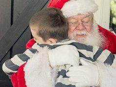 hamburg: santa hugging a young boy with a stripped shirt