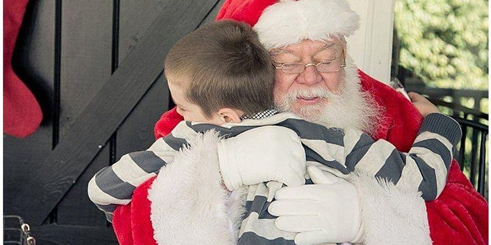 hamburg: santa hugging a young boy with a stripped shirt