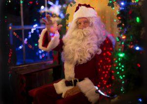 holiday: santa claus sitting waving at the camera