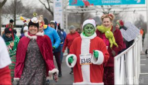 Holiday Guide: group of people dressed in christmas outfits running a race