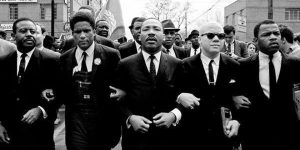 martin luther king jr. linking arms with other men in a black and white photo