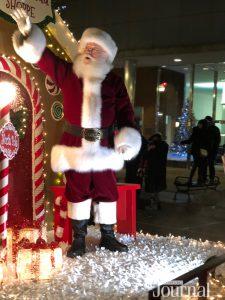 santa waving at the crowd in the christmas parade