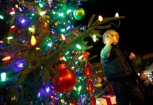 christmas tree with colorful lights and a young boy looking at it