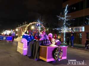"a group of characters sitting on a couch ""watching tv"" in the christmas parade"