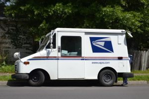 new year's: usps truck in front of green trees on the side of the road