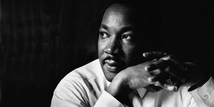 black and white image of martin luther king looking in the distance with his hands clasped