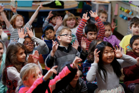 group of elementary kids raising their hands