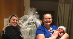 first baby: 2 nurses holding a basket full of baby items and a new born baby