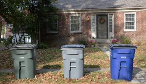 3 trash bins in front of a house