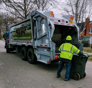 home and garden waste: a garbage truck and a waste collector