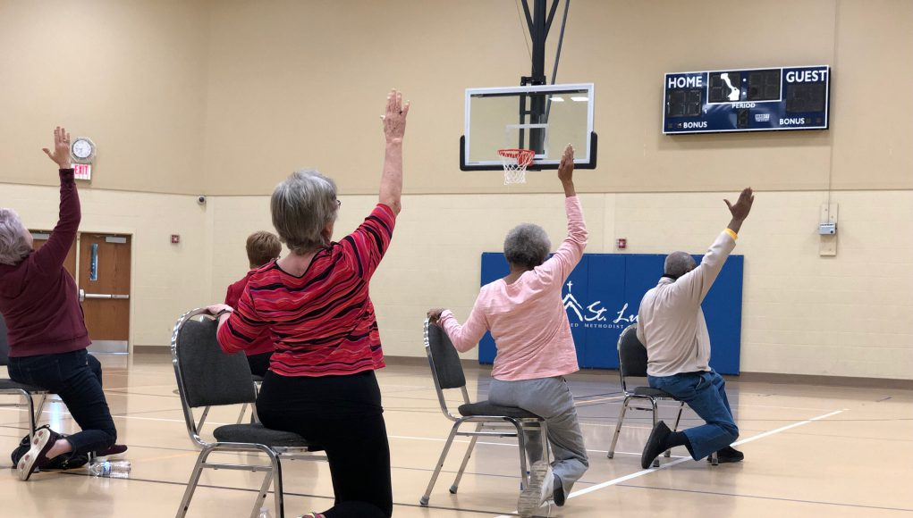 SilverSneakers: older people doing chair yoga