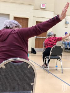 seniors performing chair yoga