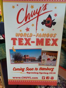 a sign that say's chuy's world-famous tex-mex with pictures of new location
