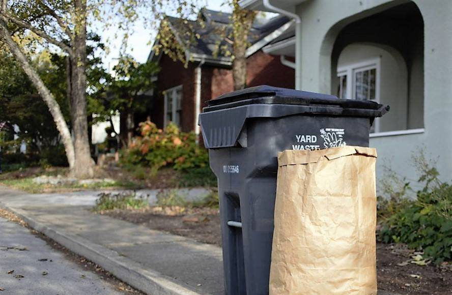 a gray trash bin with a grass clippings bag on the curb