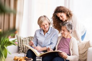 senior: A teenage girl, her mother and grandmother looking at old photographs at home. Family and generations concept.