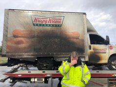 a burnt krispy kreme truck on a truck bed and a police officer in front holding his face