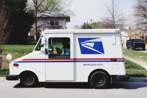 white mail truck in front of a residential house