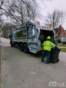 Presidents' Day: a garbage truck and a trash collector putting a herbie to dump in the truck