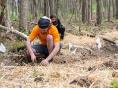 environmental: a man in an orange shirt and hat digging in the ground