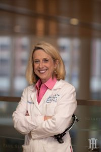 gretchen wells: woman in a pink top with a white labcoat smiling at the camera