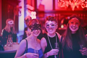 mardi gras: three women dressed up with masks