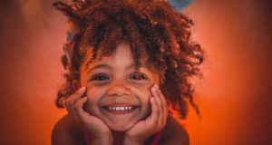 Little Ones Fundraiser: little girl smiling with a little afro and a burnt orange background