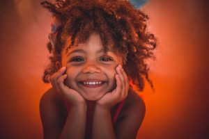 Lexus: little girl smiling with a little afro and a burnt orange background