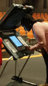Citizens Youth Academy: a young girl in a light pink cardigan working a voting machine