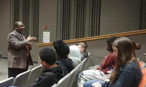 Citizens Youth Academy: group of students listening to a man speak
