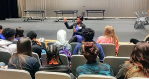 Citizens Youth Academy: woman in a purple dress with black cardigan talking to a group of students