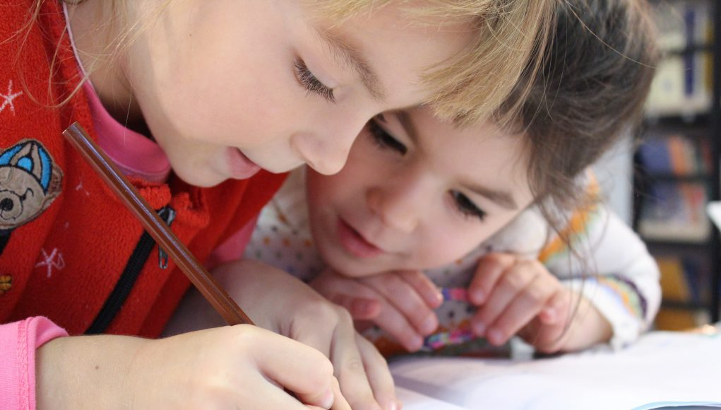 harmony day montessori school: two kids drawing on a sheet with a colored pencil
