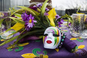 a mardi gras mask with purple, green, and yellow colors