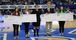 Essay Contest: four students holding checks and a woman dressed in black between them