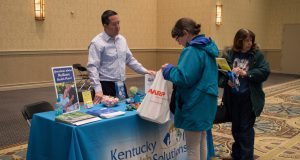 Senior: a man at a table that says kentucky health solutions on the table cloth talking with a female