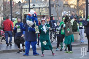Shamrock Shuffle: a blue mascot and a woman dressed like an old woman smiling at the camera