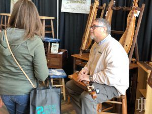 Kentucky Crafted Market: man with a wooden instrument talking to a woman