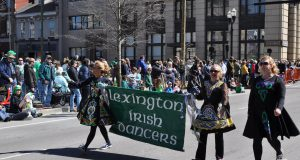 Parade: group of 3 women wearing traditional irish dancing garb holding a banner