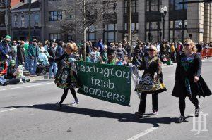 Parade: group of 3 women wearing traditional irish dancing garb holding a banner