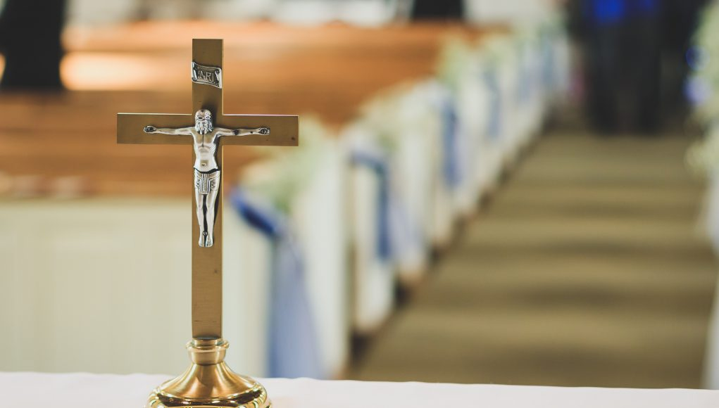 Easter Service: wooden cross on a table with a white cloth and pews